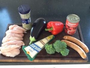 Råvarerne; kyllingeinderfilet, to store tykke pølser, aubergine, broccoli, rødpeber,hakket tomater og oregano.