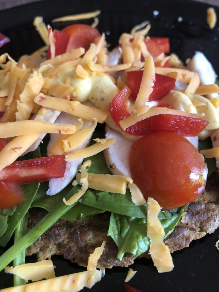 Glutenfri blomkålsbrød toppet med kylling, karry dressing, spinat, tomat, peberfrug og chili gouda.